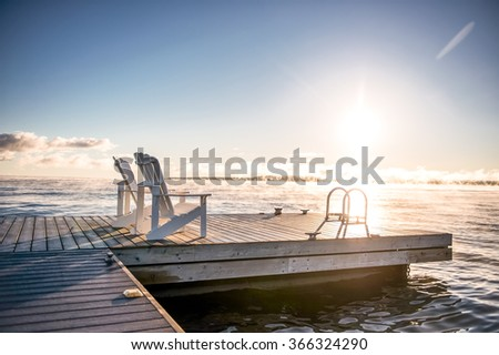 Muskoka chairs on a dock at sunrise with mist coming off the lake - stock photo