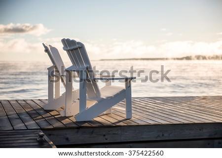 Muskoka chairs on a dock over looking lake Huron and Georgian Bay - stock photo