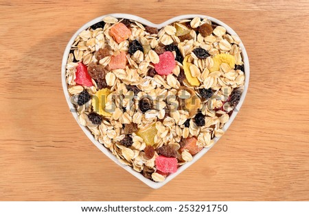 Musli  in plate in the form of heart in a wooden background - stock photo