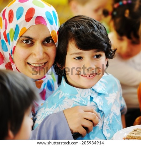 Muslim Arabic mother with children having fun at birthday party - stock photo