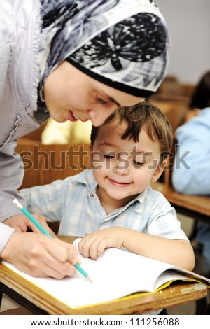 Muslim Arabic teacher working with little kid at school - stock photo