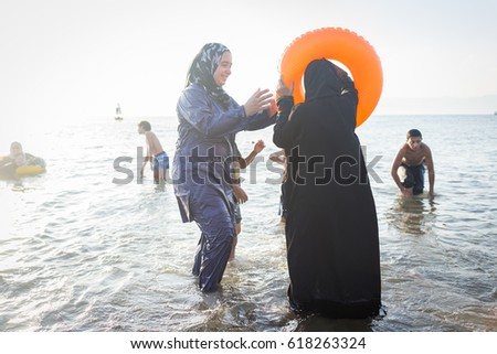 Muslim Arabic women at sea beach in burkini