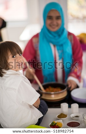 Muslim Arabic young mother and little cute son making food and having fun in kitchen at home