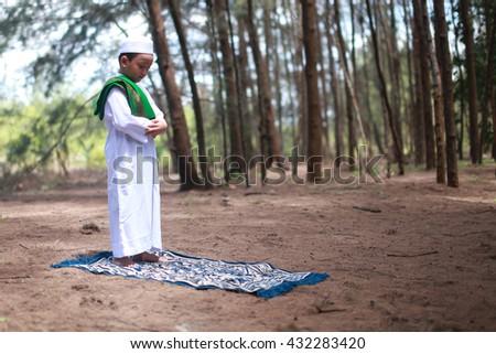 Muslim asian kid praying during the month of Ramadan - stock photo