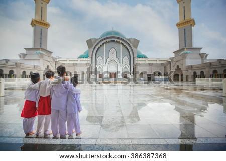 Muslim boy and Masjid Wilayah Persekutuan in Kuala Lumpur, Malaysia - stock photo
