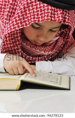 Muslim boy reading Koran - stock photo