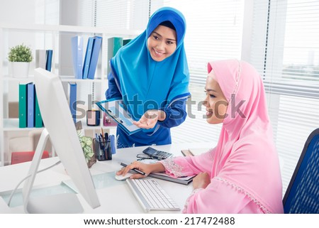 Muslim business ladies working on computer in the office - stock photo