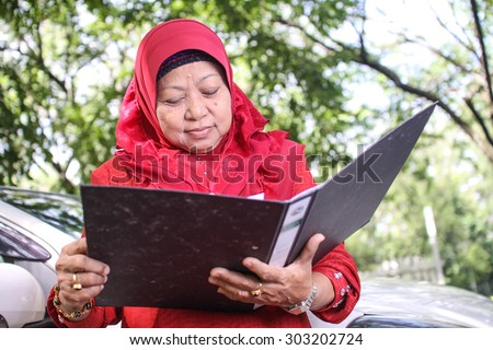 muslim business woman looking at documents in folder - stock photo