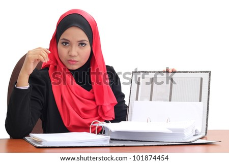 Muslim business woman writing in her note book - stock photo
