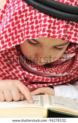 Muslim child with Koran - stock photo