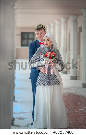 Muslim couple husband and wife are holding a bouquet of flowers - stock photo