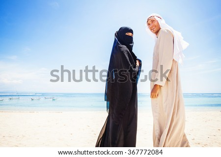 muslim couple on a beach wearing traditional dress - stock photo