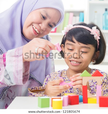 Muslim family building wooden house toy. Southeast Asian family living lifestyle. - stock photo