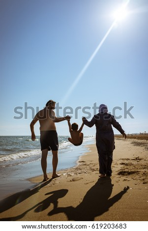 Muslim family, dad and mom with burkini on the beach walking near sea