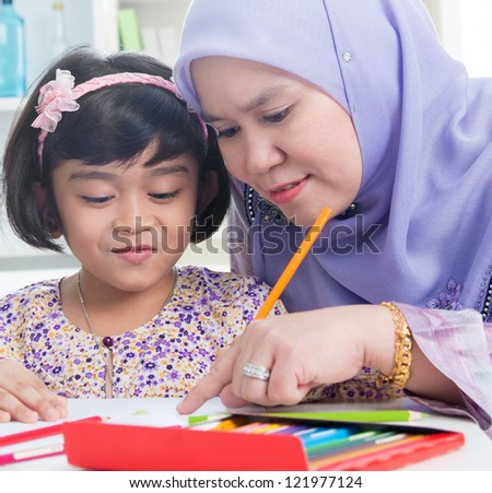 Muslim family drawing picture at home. - stock photo