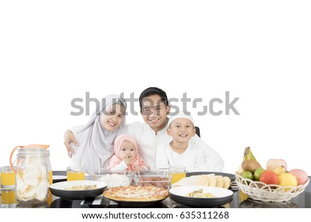 Muslim family having meal at dining table while smiling at the camera, isolated on white background