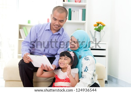 muslim family using tablet computer - stock photo