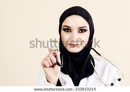 Muslim female doctor in white lab coat holding a stethoscope. She is wearing a hijab - stock photo