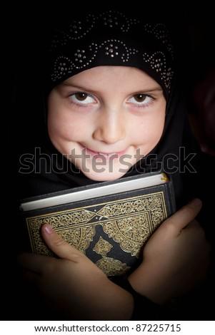 Muslim girl holding Holy Book Koran - stock photo