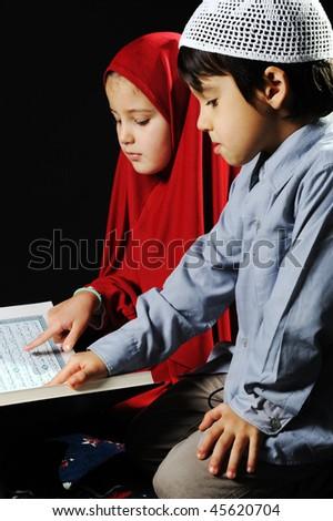 Muslim girl on black background reading Koran - stock photo