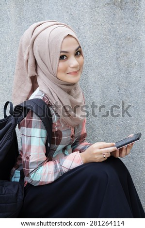 Muslim girl student with her tablet  - stock photo