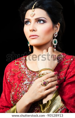 Muslim Indian bride wearing a red bridal dress, portrait of a beautiful Indian bride - stock photo
