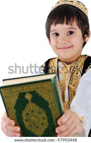 Muslim kid holding holy Qoran - stock photo