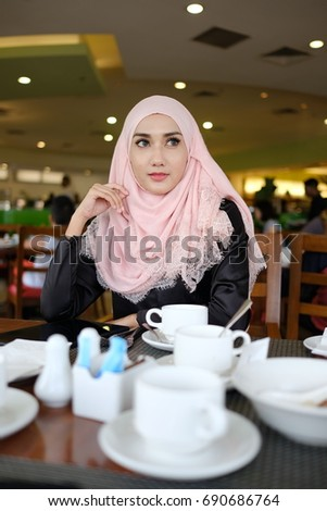 Muslim lifestyle woman using tablet at restaurant. Lifestyle conceptual