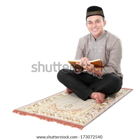 muslim man holding and reading quran isolated over white background - stock photo