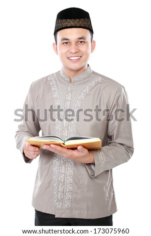 muslim man holding quran isolated over white background - stock photo