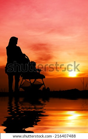 Muslim mother and baby walking during sunset - stock photo