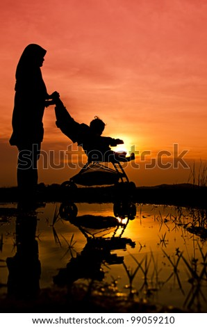 Muslim mother and baby walking during sunset