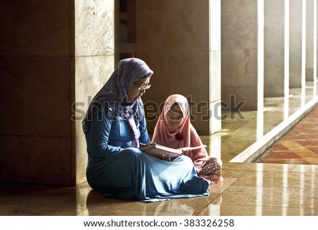 Muslim mother teach her daughter reading koran inside the mosque - stock photo