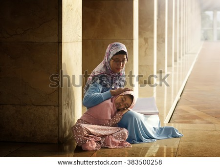 Muslim mother teach her daughter reading koran inside the mosque - stock photo