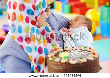 Muslim mother with baby at birthday party - stock photo