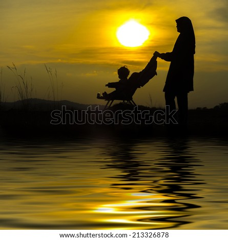 muslim's mother with his son in silhouette during sunset. digital compositing with colour tone, water reflection and ripple effects. - stock photo