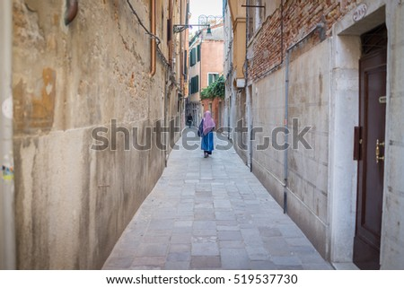 Muslim traditional woman visiting old city Venice in Italy