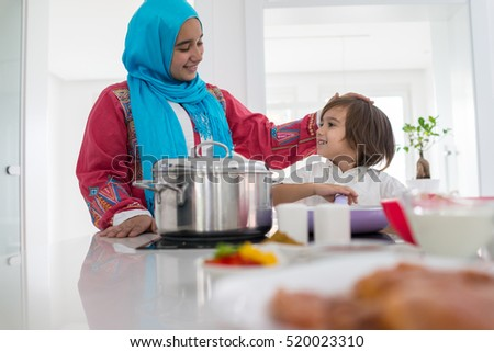 Muslim traditional woman with little son in modern white kitchen