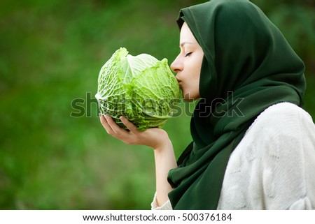 Muslim Vegan Woman with Veil Kissing a Savoy Cabbage