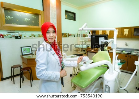 Muslim woman dentist from Indonesia pose in her clinic