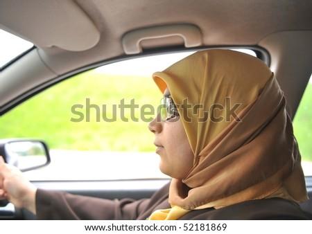 muslim woman driving a car - stock photo