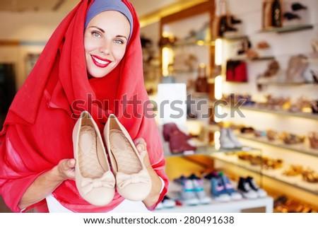 muslim woman in hijab choosing shoes in a shop - stock photo