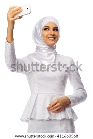 Muslim woman in white dress making selfie isolated - stock photo