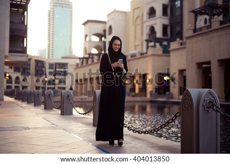 Muslim woman messaging on her mobile phone. - stock photo