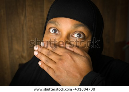 Muslim woman of African descent holding her hand in front of her mouth - stock photo