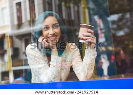 Muslim Woman Talking on Mobile Phone in a Cafe - stock photo