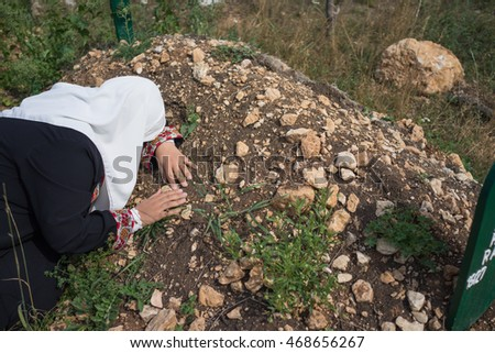 Muslim woman visiting grave in cemetery