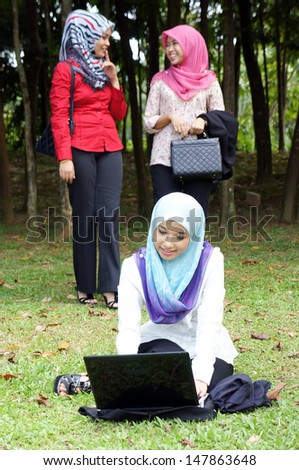 Muslim young woman using a laptop while sitting outside - stock photo