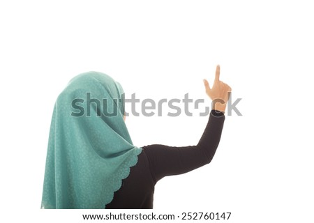 Muslimah businesswoman pointing at the wall isolated white background.