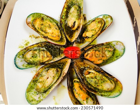 mussel from new zealand escalloped with garlic butter served on a white oval shaped plate - stock photo